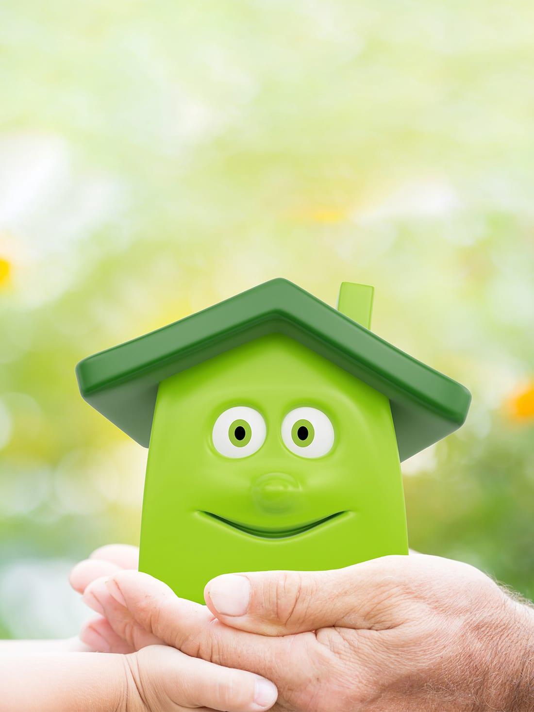 Family holding eco cartoon house in hands against green spring background. Environment protection concept