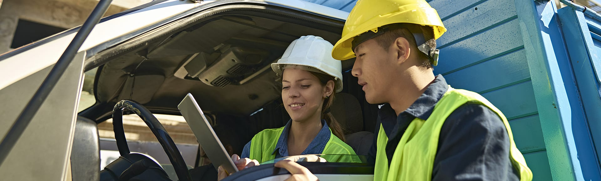 Low angle view of construction workers discussing over digital tablet. Coworkers are examining checklist at construction site. They are wearing protective workwear.