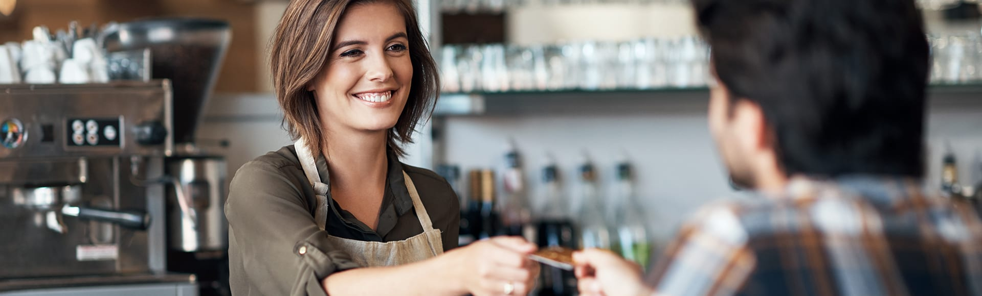Shot of a cheerful female bartender receiving a card as payment from a customer inside of a restaurant