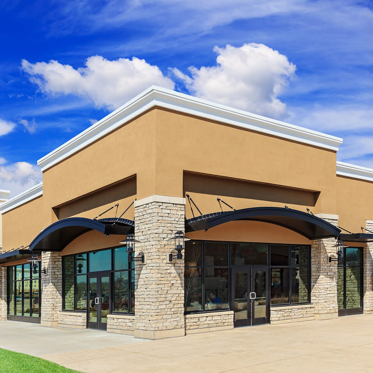 New commercial development featuring a street view of a Strip Mall with green grass, sidewalk and patio space. Blue sky and clouds are in the background.