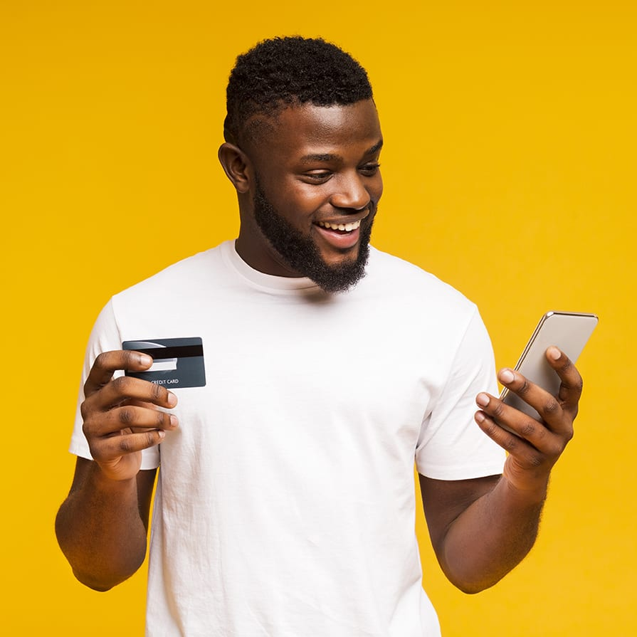 happy guy looking at phone and holding debit card in other hand