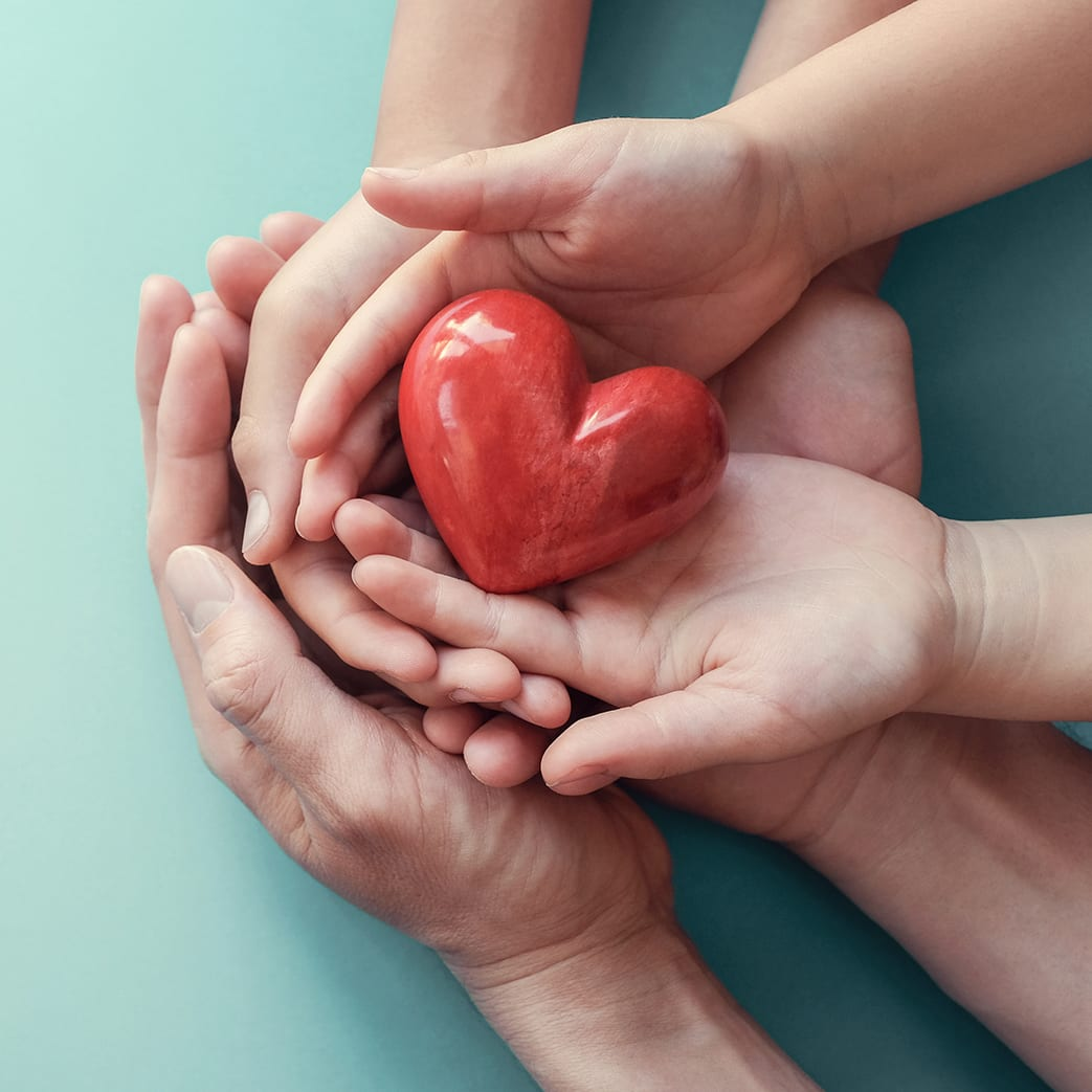 Adult and child hands holding a red heart on an aqua background to signify the importance of heart health, donations, CSR concepts, world heart day, world health day, and family day