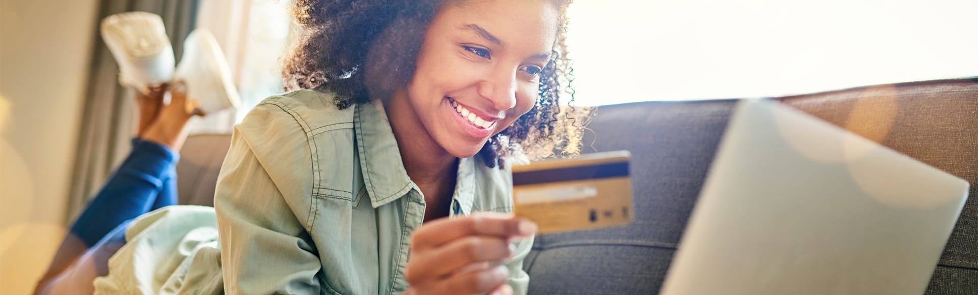 woman on couch looking at debit card and computer smiling
