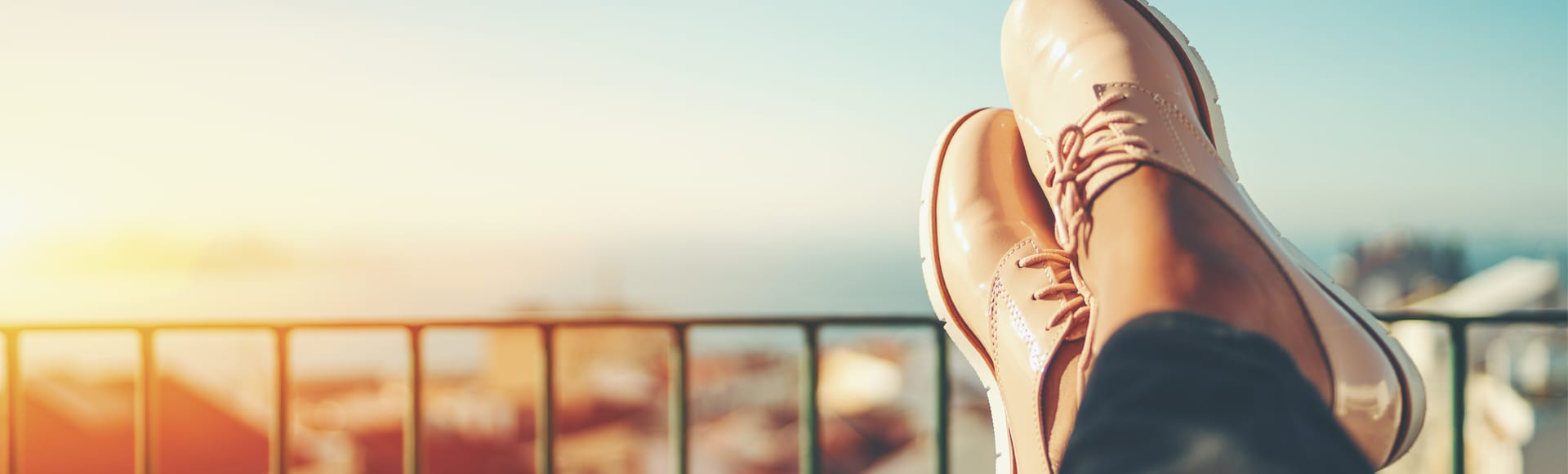 Female feet with glossy pale pink shoes relaxing on wooden table and touristic european city near sea with multiple houses in blurred background with copy space for advertising, logo or your texts