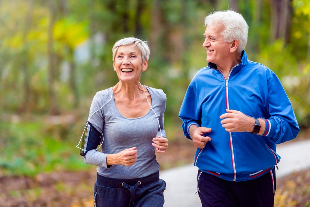 happy older couple taking jog down trail