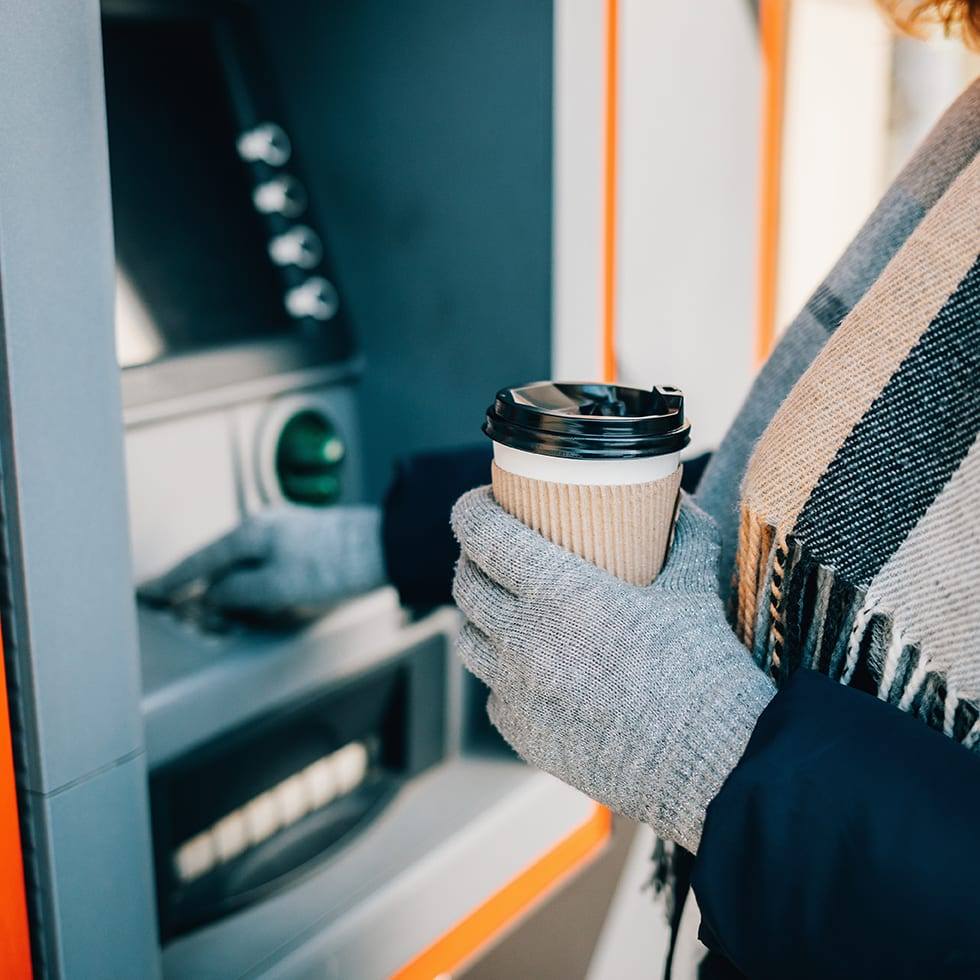 Close-up of young woman in warm clothing holding coffee and using an ATM on city street in winter day.