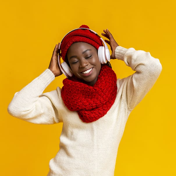 Emotional winter girl listening to music with closed eyes, using wireless headset, yellow background