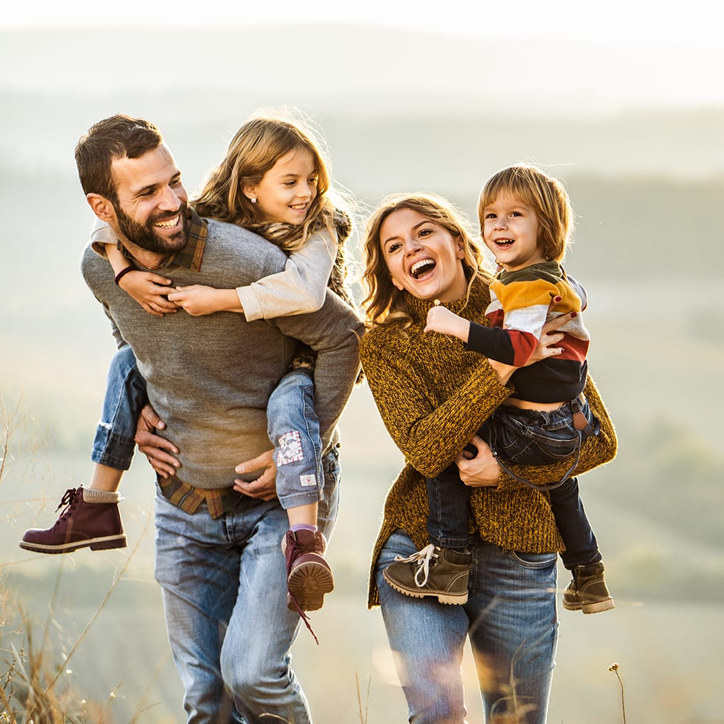 A young happy family with parents and two kids enjoying an autumn walk on a hill