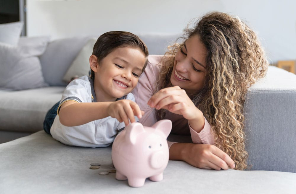 mom and daughter adding savings to piggy bank