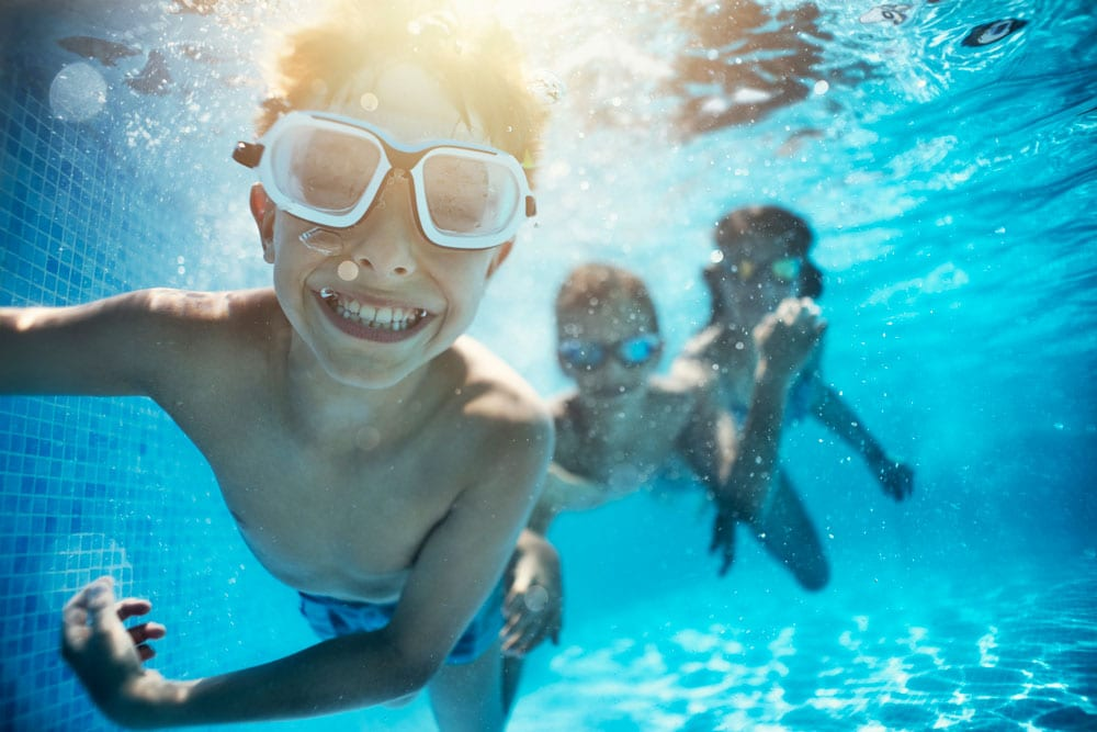 kids swimming under water excited on vacation