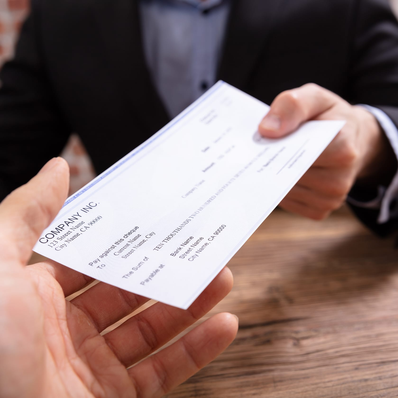 Close-up Of Businessman's Hands Giving Cheque To Other Person In Office