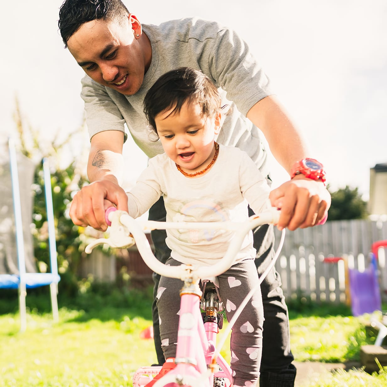 Maori father helping her daughter to ride bicycle in backyard.