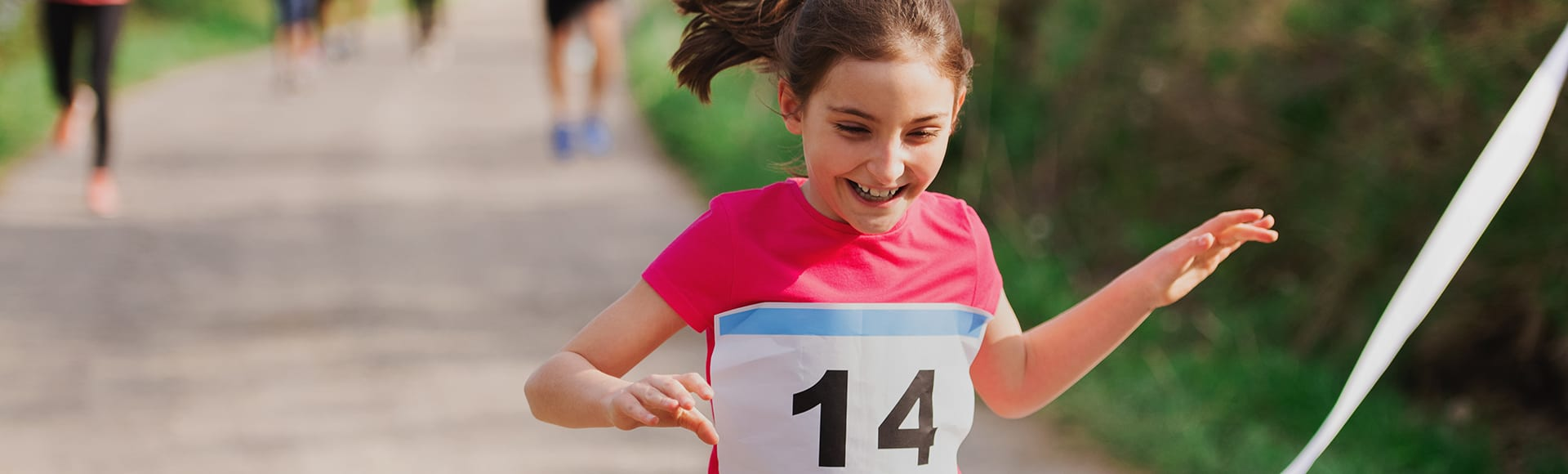 A small girl runner crossing finish line in a race competition in nature.