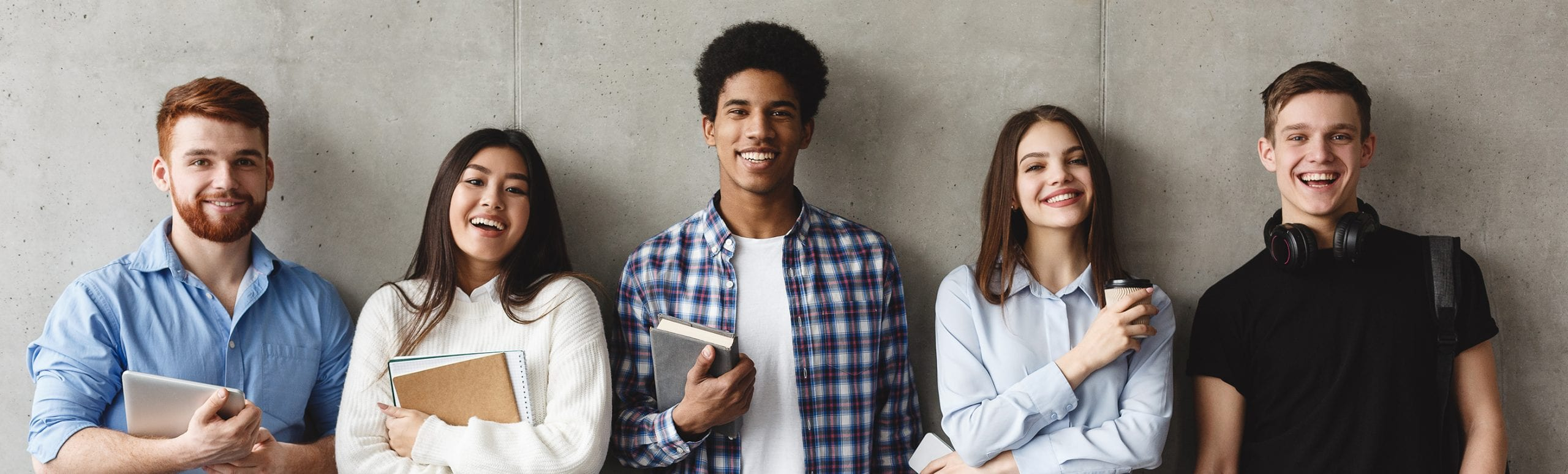 College students with books smiling to camera over grey wall, having break