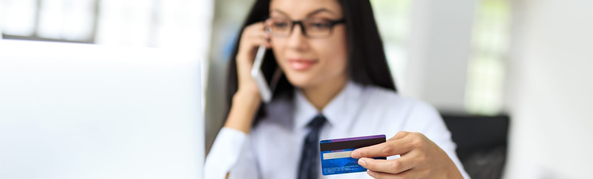 A smiling business woman on the phone holding an aesthetic credit card in hand