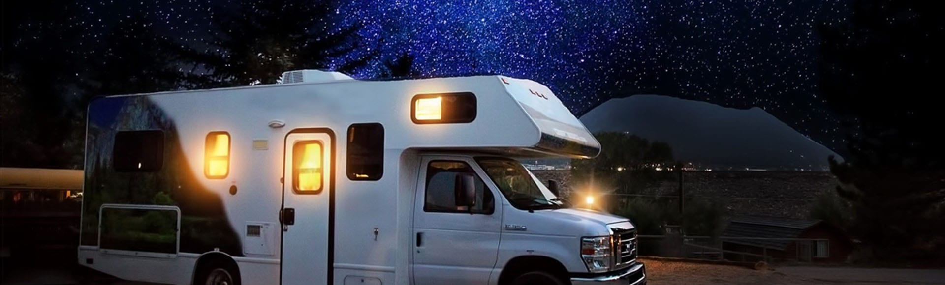 Recreational vehicle fifth wheel trailer in campsite with campfire and Christmas lights and decorations at dusk or night.