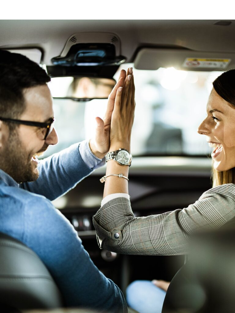 Image of a man and a woman in the front seat of a car. They are giving each other a high five and they are laughing.