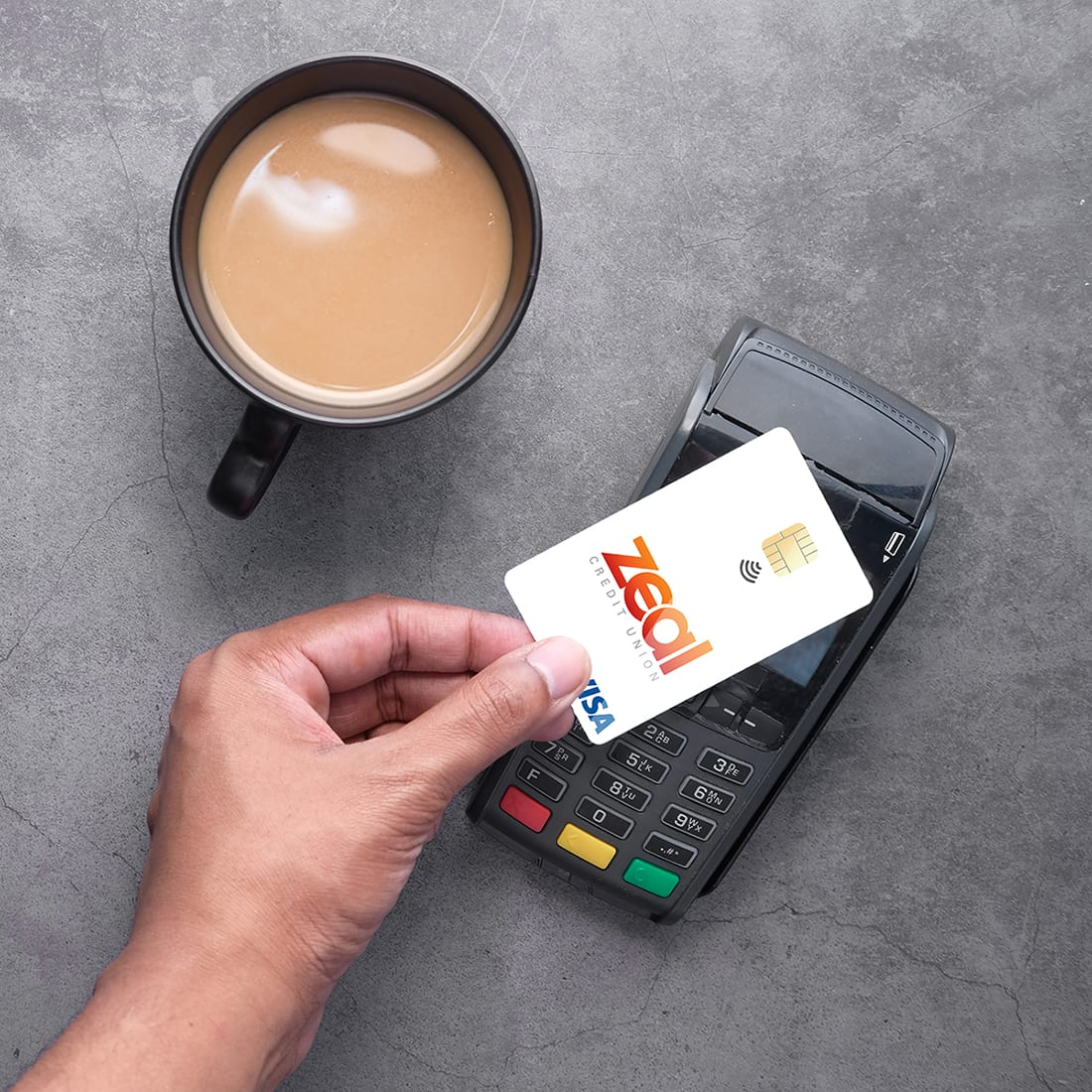 Zeal Tap to Pay. Hand holding Zeal credit card over wireless payment system.