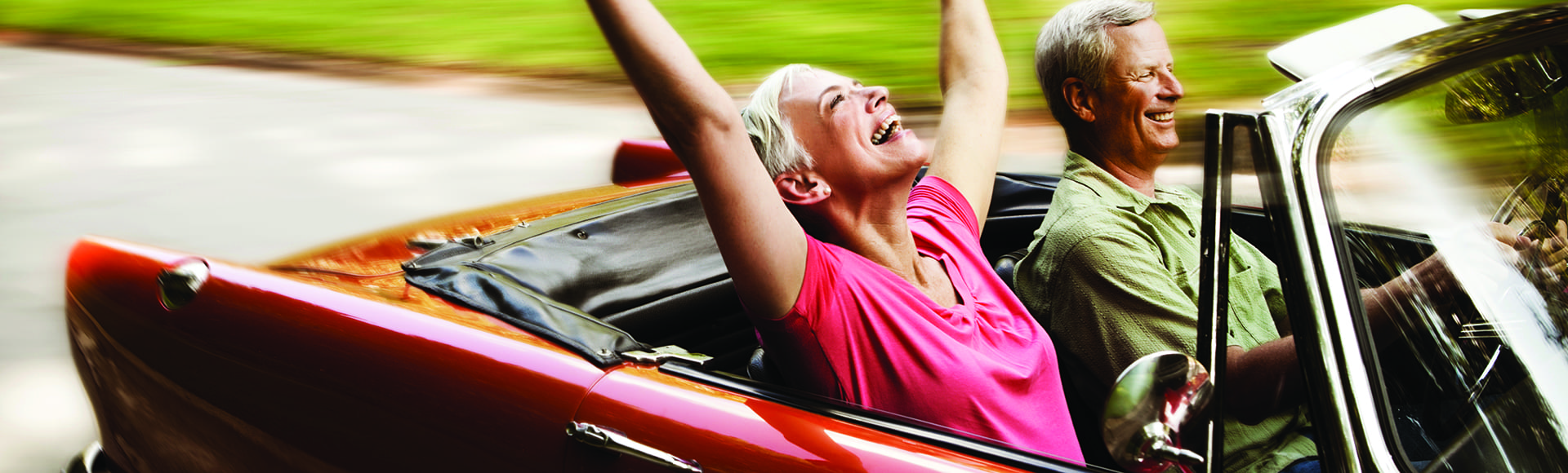 Senior woman throws her arms in the air while her husband drives her down a road in their convertible. Horizontal shot.