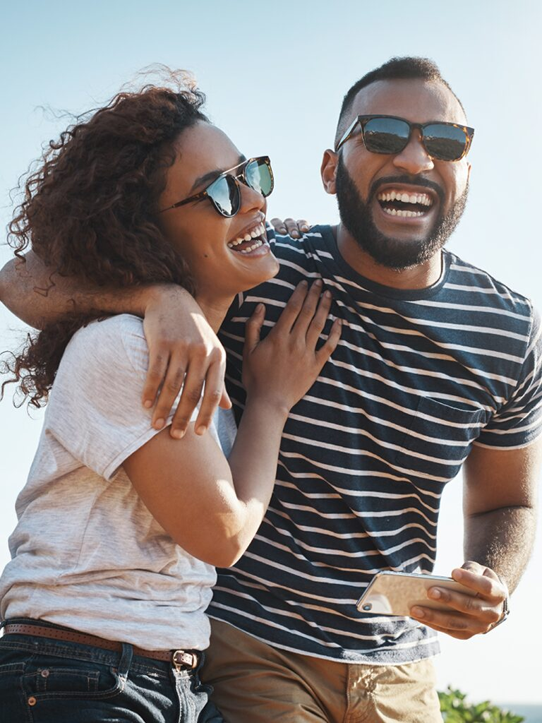 A man and a woman are smiling and laughing. He has his arm wrapped around her shoulder. They are outside on a sunny day.
